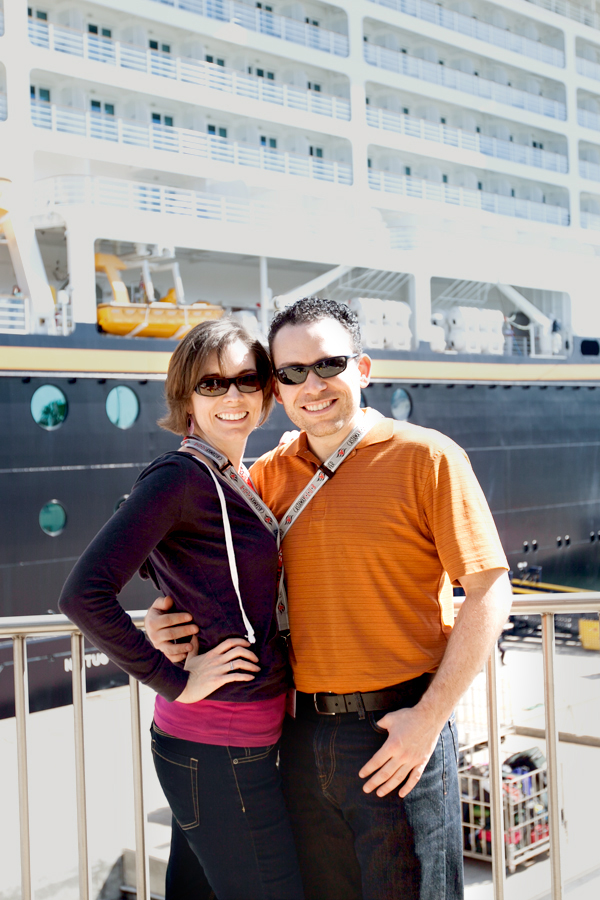 husband and wife in front of a disney ship