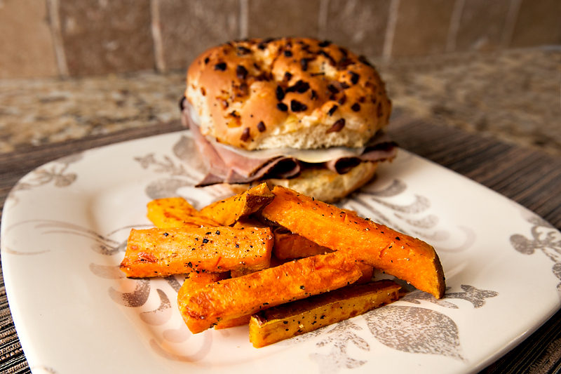 oven baked sweet potato fries with salt and pepper and a roast beef onion roll sandwich