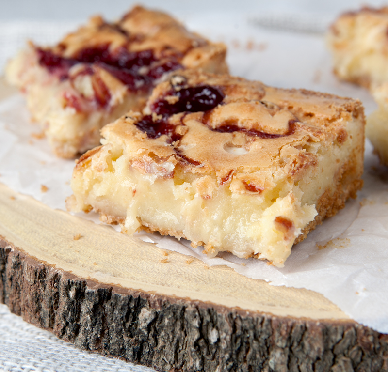 Ooey gooey chewy white chocolate raspberry swirl blondies. These delectable cookie bars has a thin crispy crust on the outside with a gooey vanilla white chocolate center, swirled with raspberry! A sweet graham cracker crust allows makes them slice like a dream.