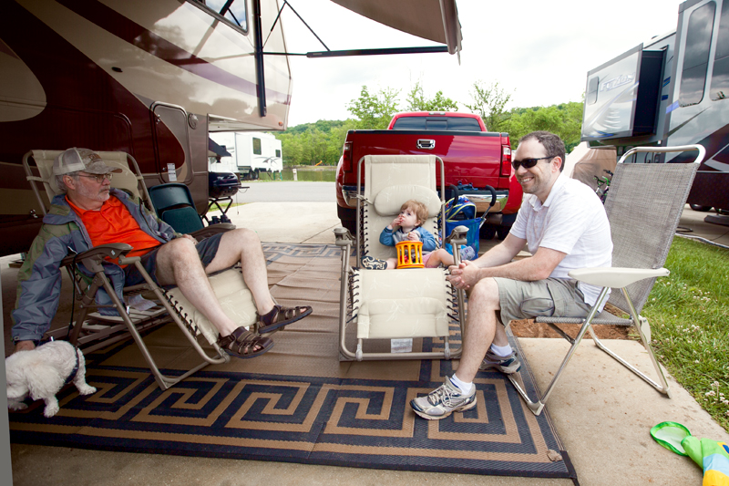 family-sitting-outside-camper