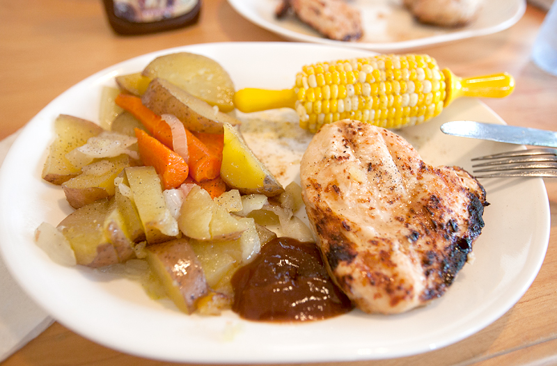 grilled chicken dinner with corn on the cob, potatoes, and carrots