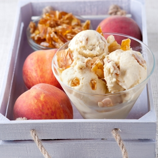 This homemade ice cream is SUMMER in a bowl!! Fresh peaches cooked and pureed with honey are blended into a smooth vanilla base with homemade crunchy almond praline pieces.