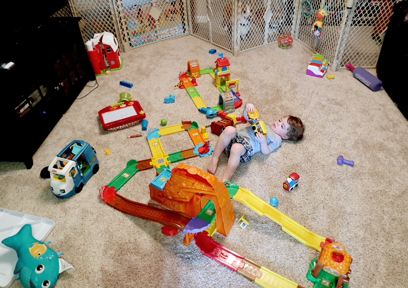 toddler-playing-with-smart-wheels-train-tracks