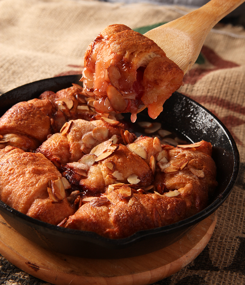 Hot crescent dumplings filled with cherries and covered in a sweet cola glaze and sliced almonds.