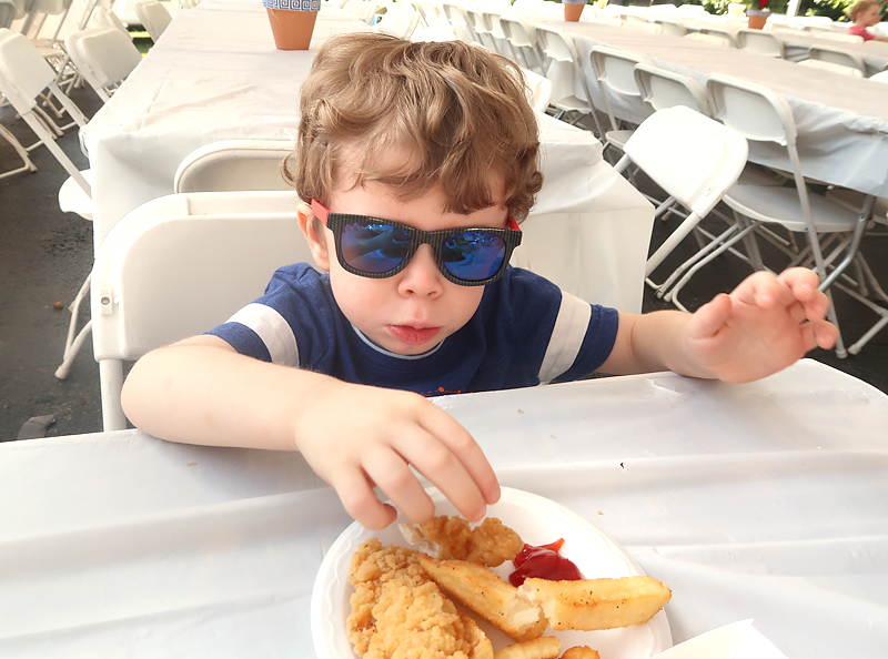 toddler with sunglasses eating chicken and fries