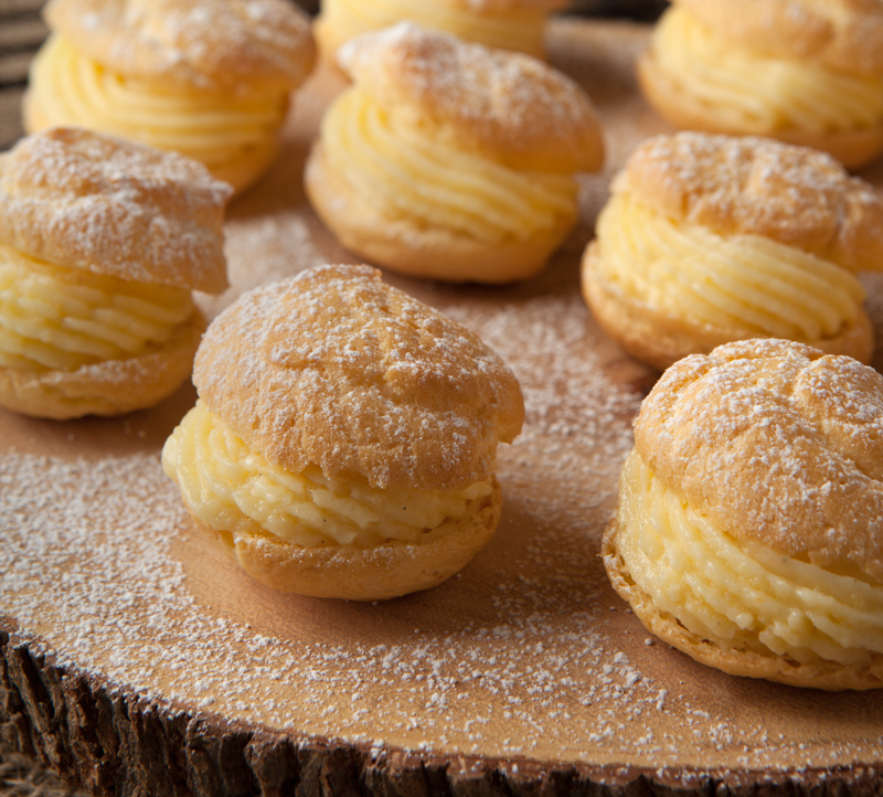 A simple pate a choux dough cream puff recipe filled with a light orange pastry cream and drizzled with chocolate. Chocolate drizzled orange cream puffs are a delightful dessert that's not too heavy!