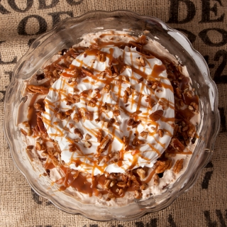 Chocolate turtle trifle - layers of chocolate cake, homemade caramel mousse, pecans, caramel drizzle, and whipped cream make this one amazing dessert that feeds a crowd!