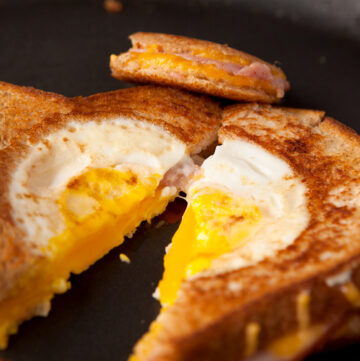 Easy dinner or breakfast idea - eggs in a basket grilled ham and cheese sandwiches. Filling, loaded with protein, and you can use fun cookie cutters for the kids!