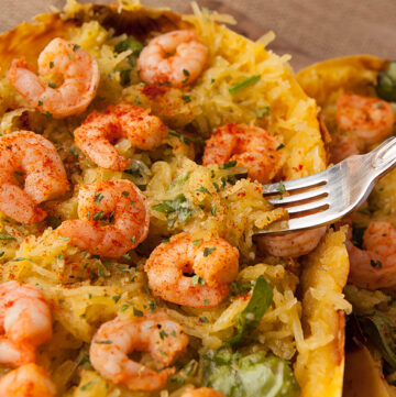 Fantastic low carb dinner idea! Roasted spaghetti squash is mixed with pesto, parmesan, garlic, and spinach and served with flavorful sauteed shrimp!