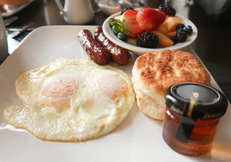 Eggs with a biscuit, sausage links, and fresh fruit at Aviles Restaurant in St. Augustine