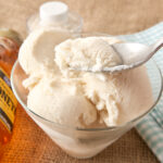 A dish of creamy homemade honey vanilla ice cream being spooned out.
