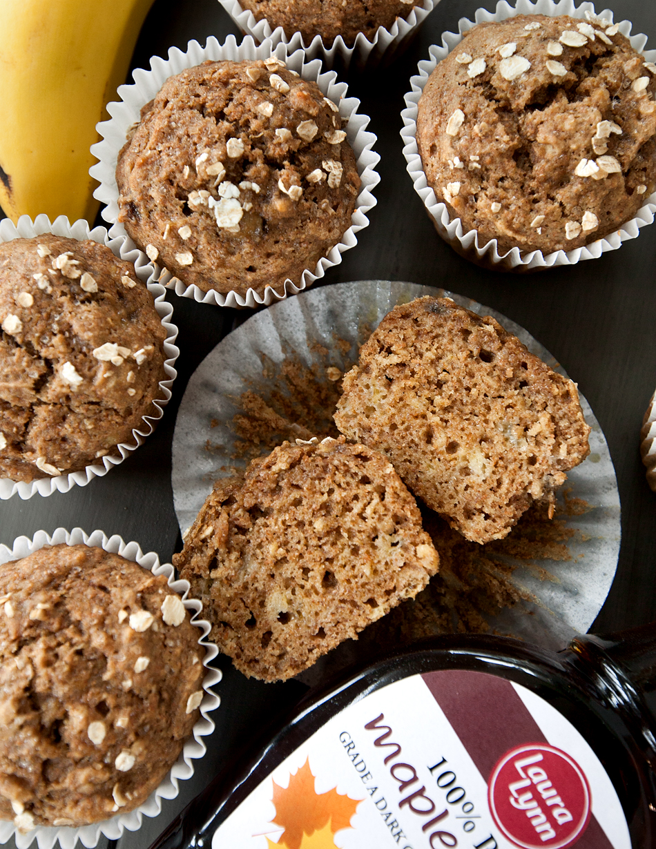 overhead view of whole wheat banana and oat muffins with maple syrup bottle