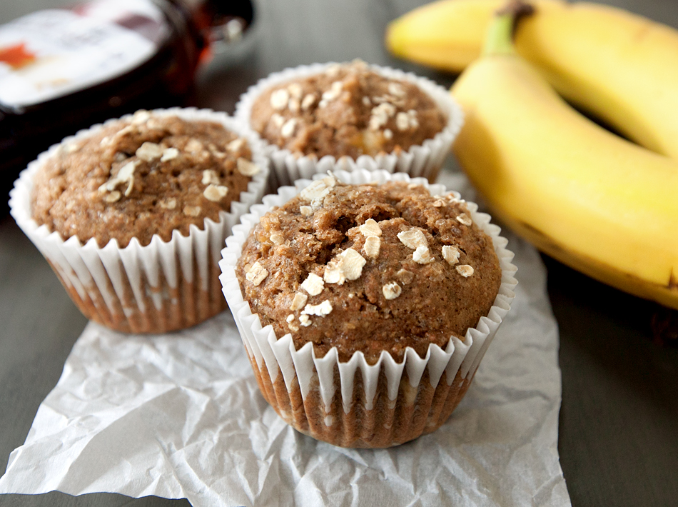 3 banana oat muffins shown with unpeeled bananas and maple syrup