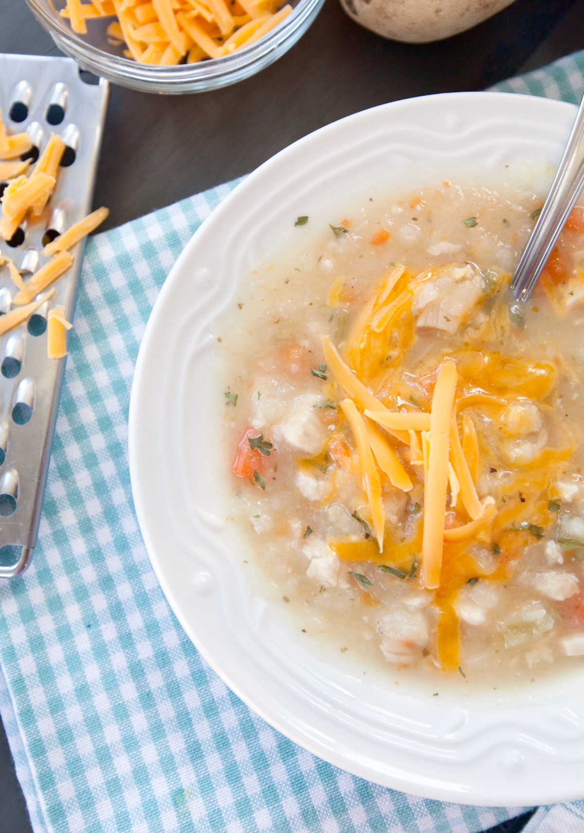 Close up view of chicken potato soup with shredded cheese