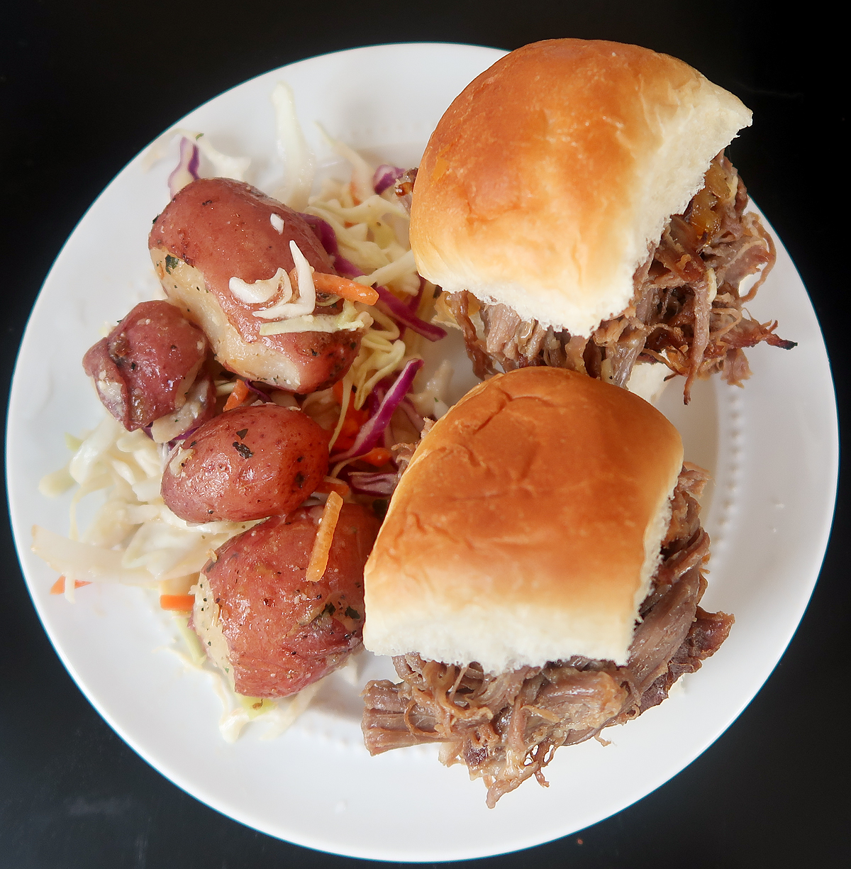 Overhead flat lay of French onion beef sliders with potato slaw