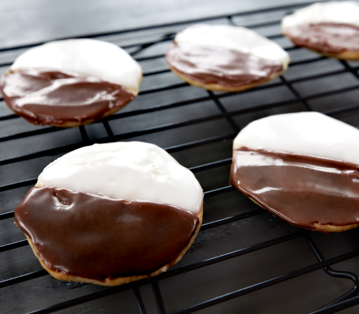shiny black and white cookies on a cooling rack