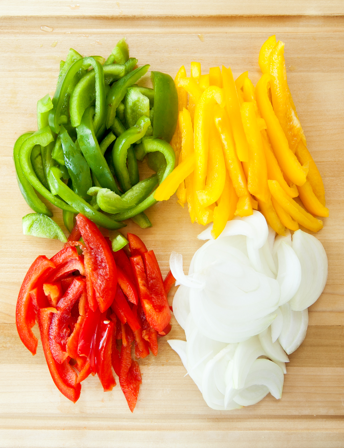 overhead view of red, green, and yellow bell peppers and onions on a cutting board