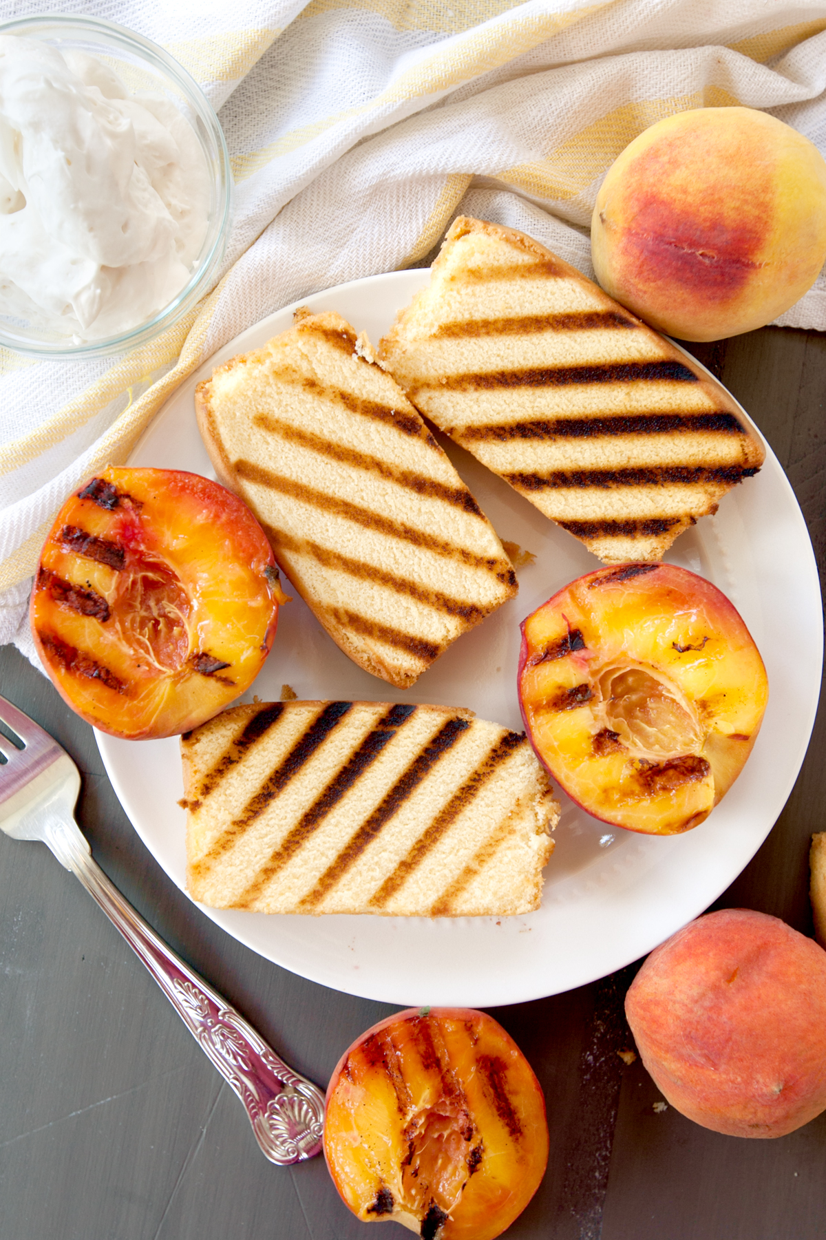 overhead photo of a plate of grilled pound cake slices and grilled peaches with a bowl of whipped cream