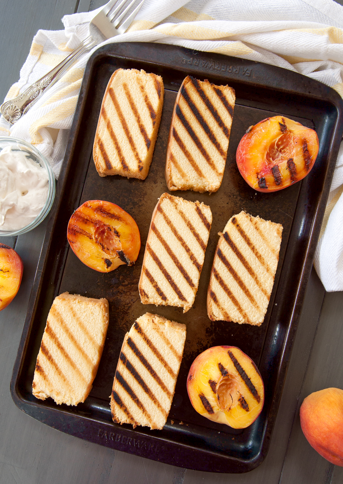 overhead photo of a baking tray full of slices of grilled pound cake and peaches