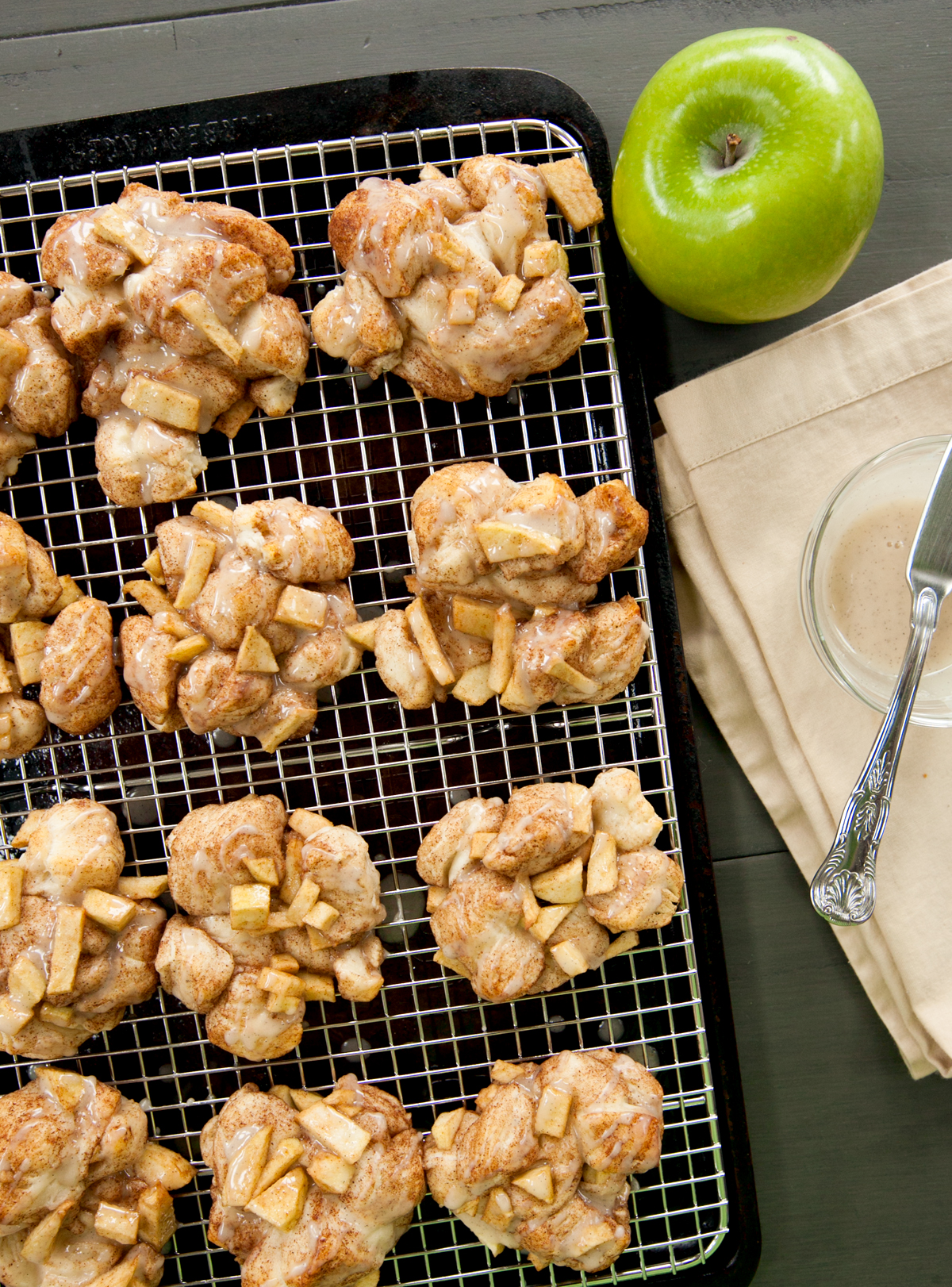 overhead view of baked apple fritters drizzled with vanilla glaze