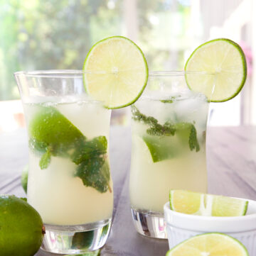 two non alcoholic mojitos with lime slices and mint leaves