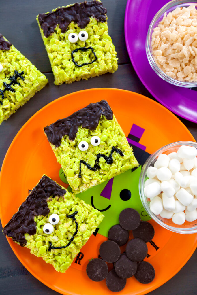 Overhead view of green rice krispies treats decorated to look like Frankenstein faces
