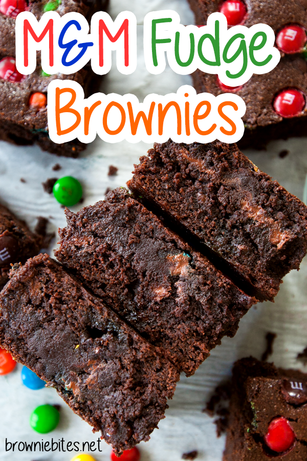 A cross-section of very thick and fudgy brownies with chocolate inside and M&Ms, with text for Pinterest.