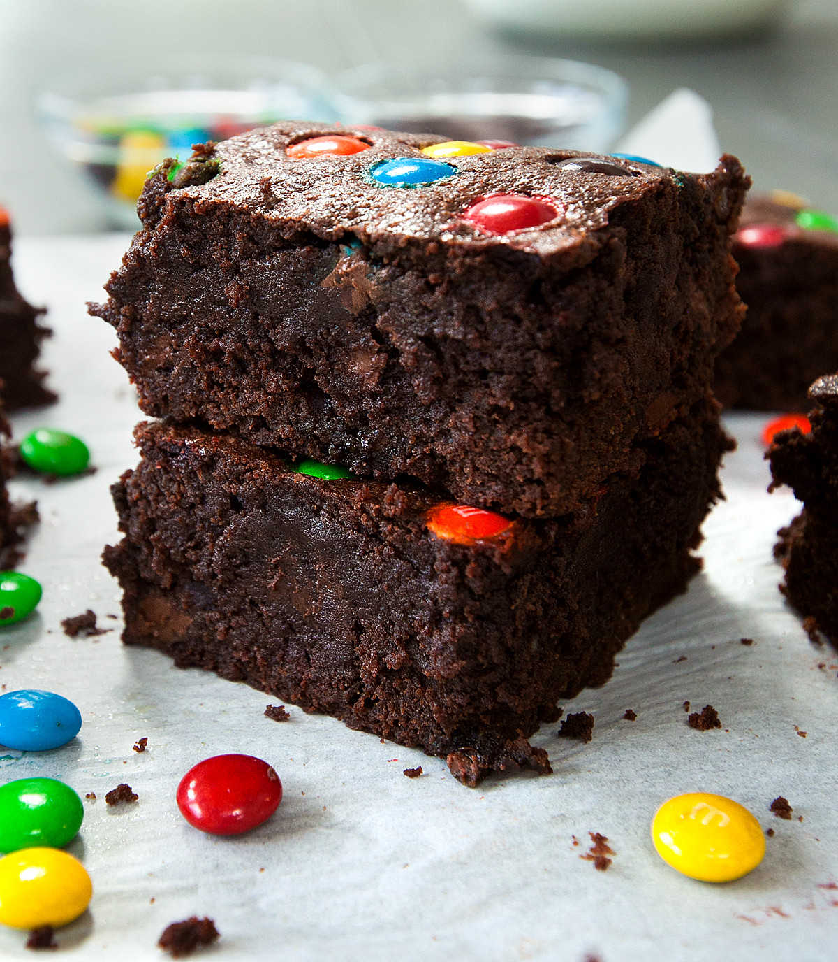 A stack of two very thick and delicious looking brownies with M&Ms scattered around