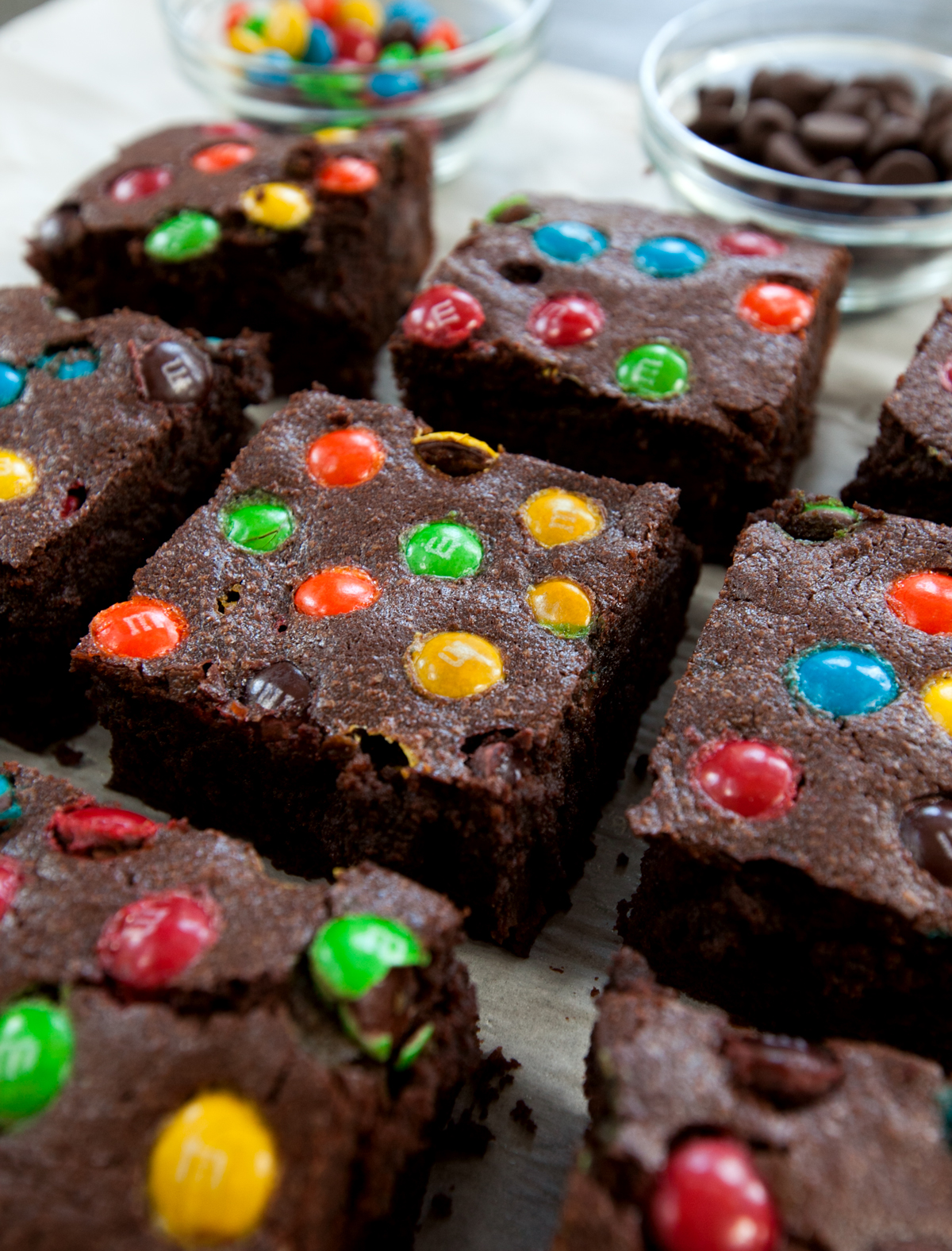 An angled view of moist and fudgy brownies topped with M&M candies.