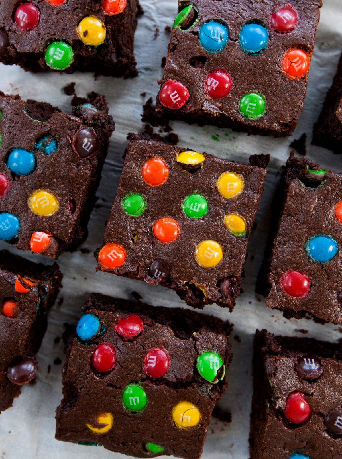 An overhead view of fudge brownies dotted with M&Ms