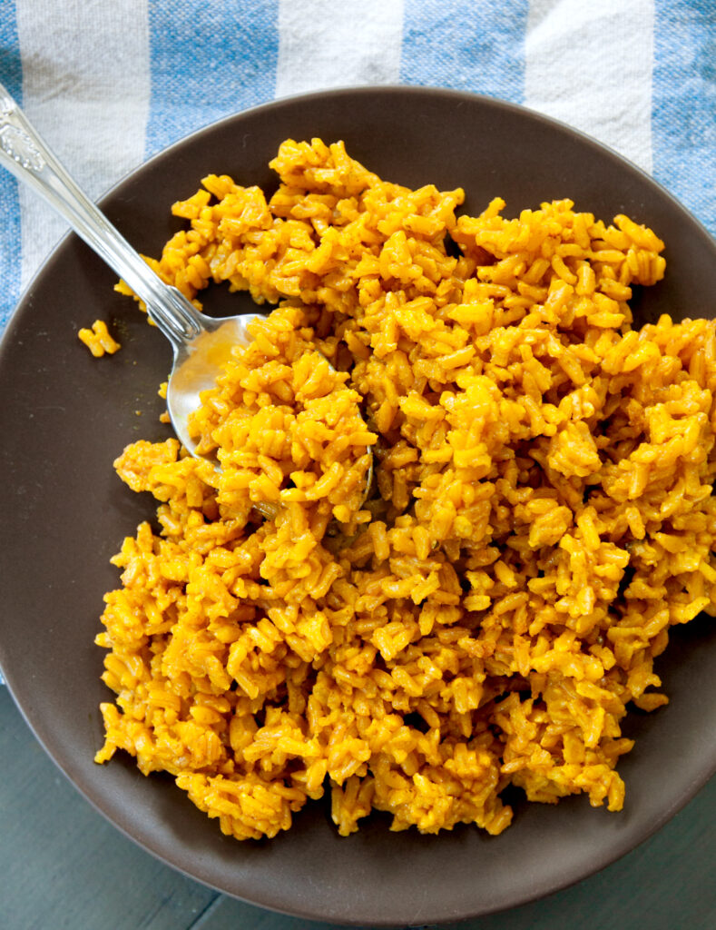 an overhead view of a bed of turmeric rice with a spoon tucked inside