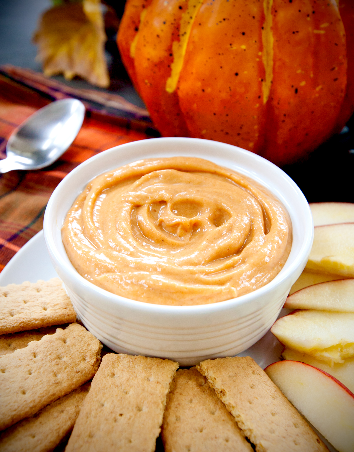 A bowl of cream cheese pumpkin dip with graham crackers and apple slices for dipping.