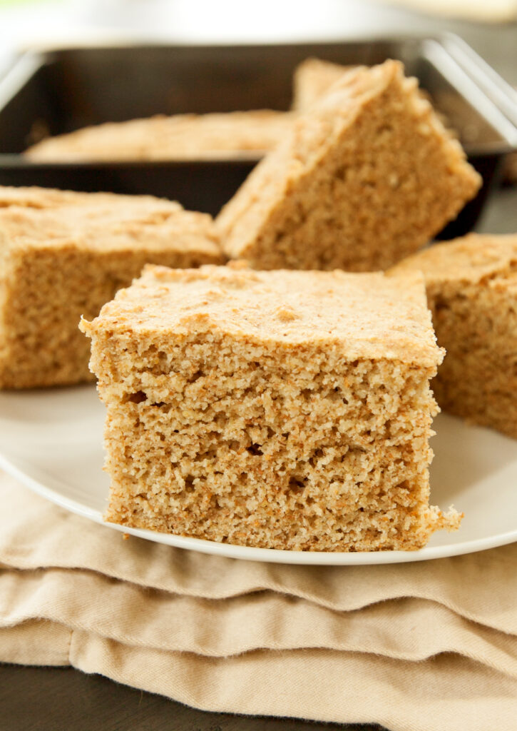 A nice thick slice of healthy cornbread sits on a plate.