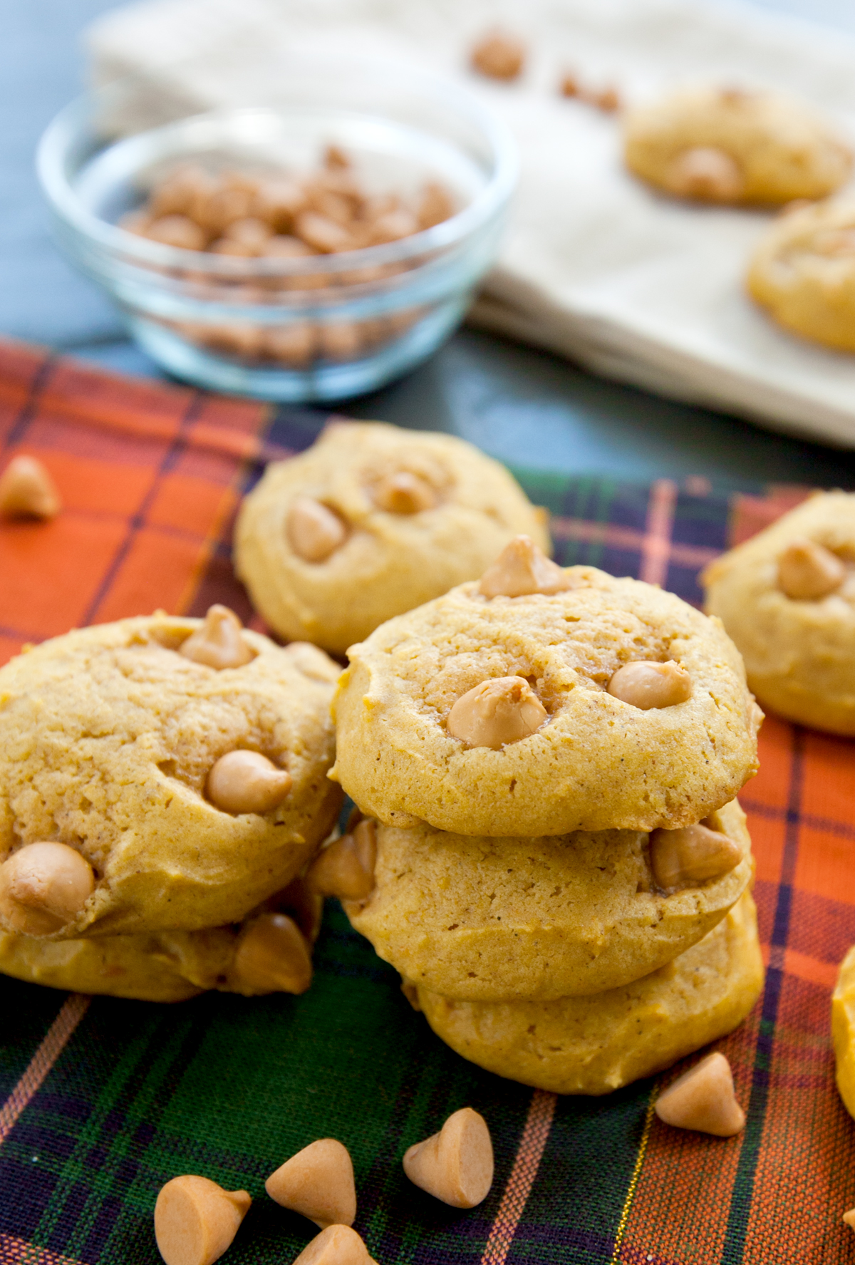 A small stack of pumpkin butterscotch cookies with a bowl of butterscotch chips blurred in the background.