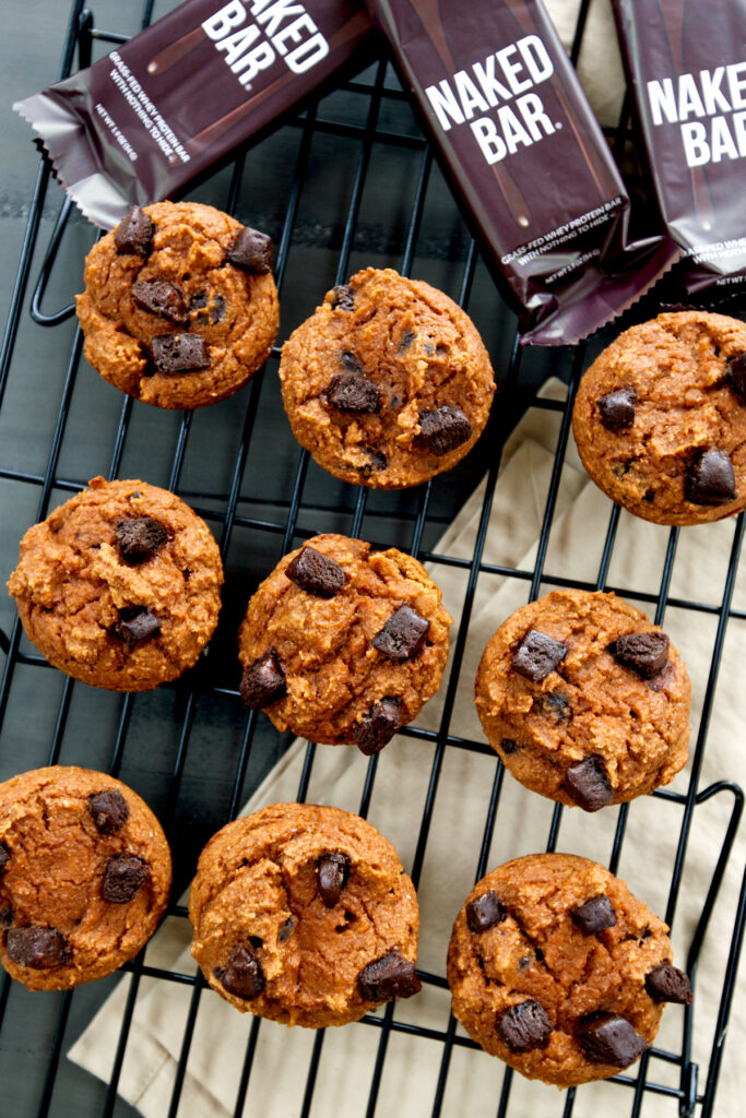 Overhead view of a cooling rack filled with protein pumpkin muffins with chocolate chunks